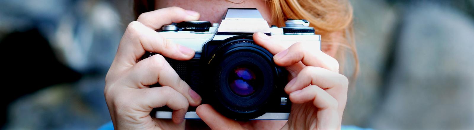 Eine Frau mit einem Fotoapparat vor dem Gesicht.