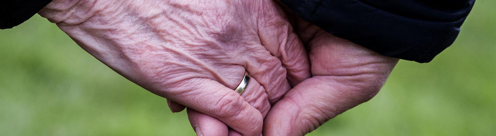 Zwei Hände halten einander fest, ein Ehering ist zu sehen.