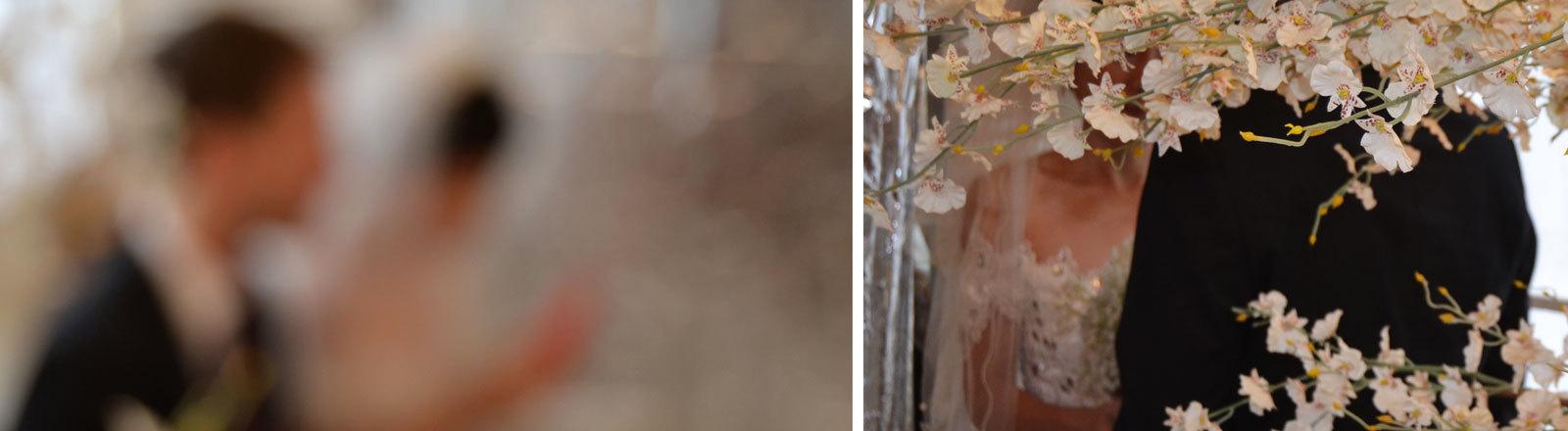 Ein Hochzeitspaar verschwommen im Hintergrund. Sie trägt ein Brautkleid, er einen Anzug.