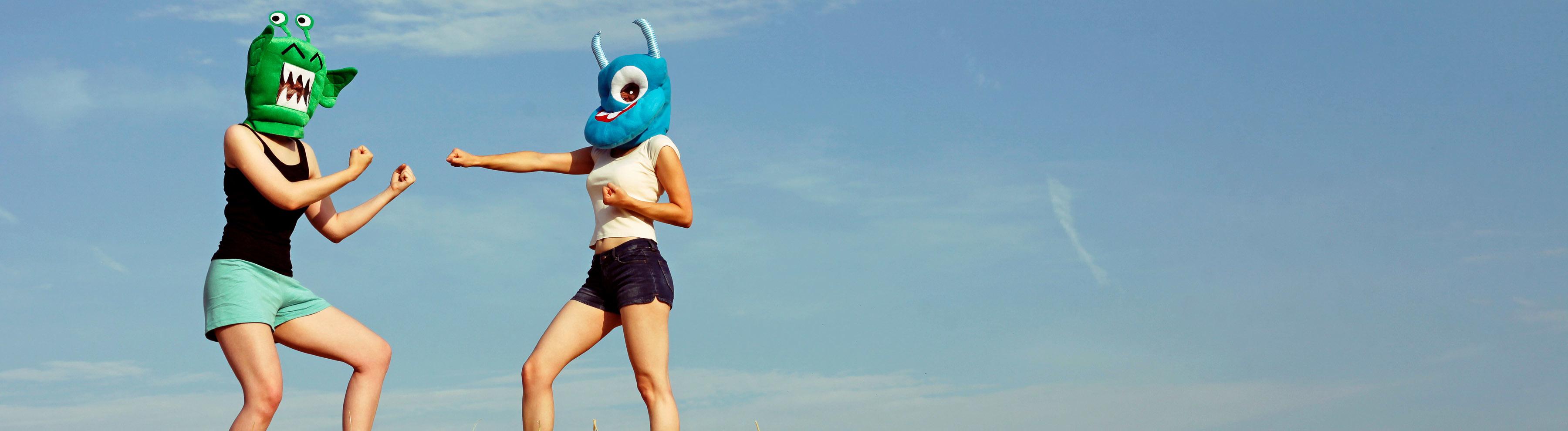 Zwei Menschen mit Monstermasken boxen.