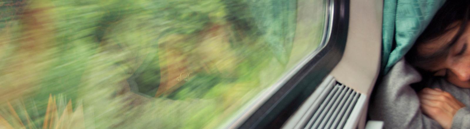 Eine Frau schläft in einer Bahn an eine Fensterscheibe gelehnt