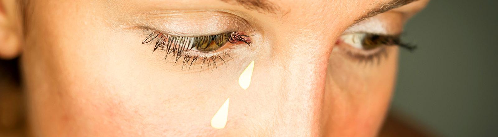 Eine Frau vergießt symbolisch Tränen, die ihr ins Gesicht geklebt wurden.