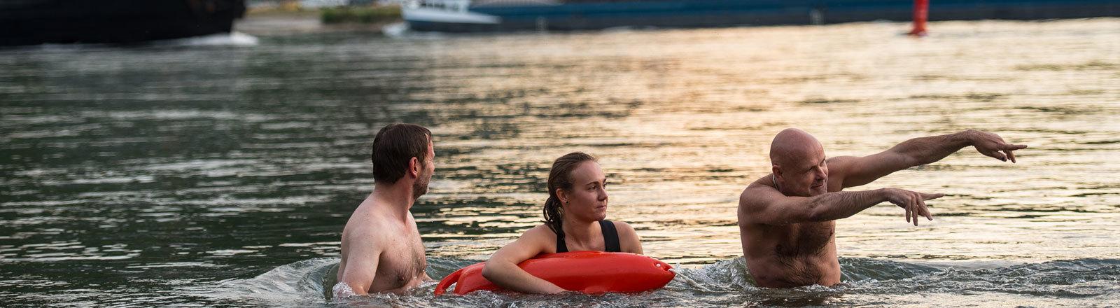 Der Leiter der Stromschwimmschule «Cubalido», Dirk Melzer (r-l), zeigt Katharina Dauer (Rettungsschwimmerin, DLRG Kaub-Loreley) und einem Teilnehmer am 29.07.2016 in Kaub (Rheinland-Pfalz) die Schwimmrichtung an.