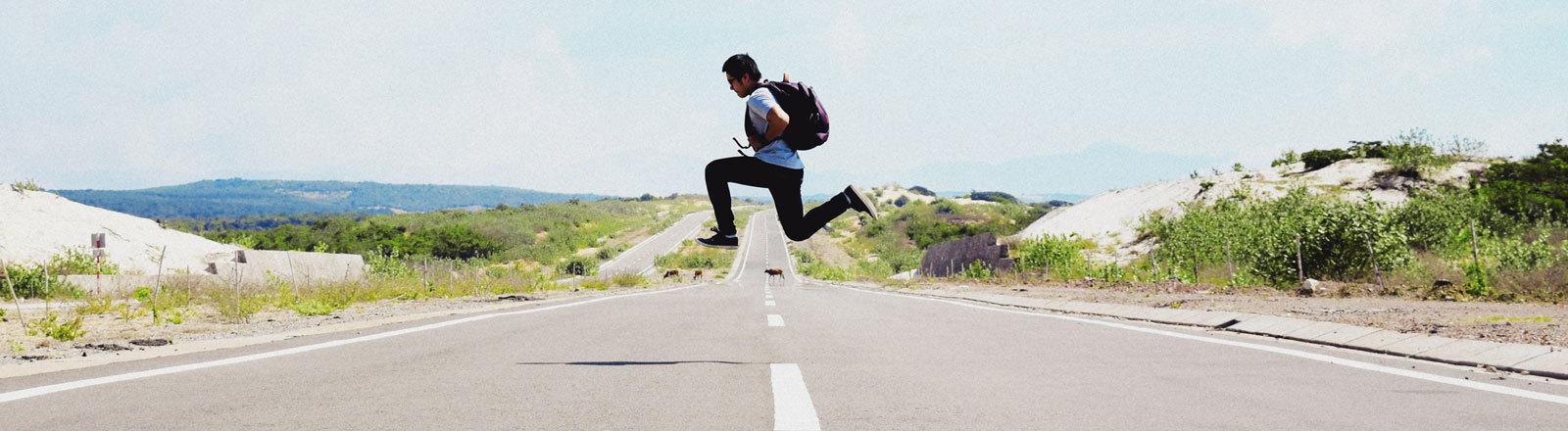 Mann springt über Mittelstreifen.