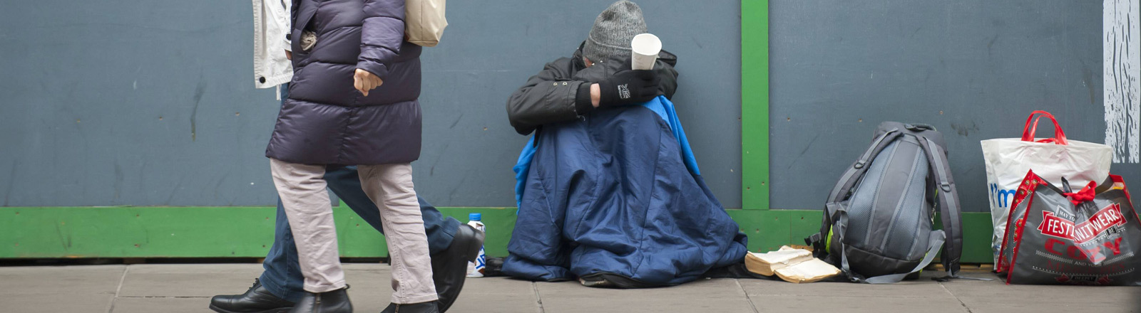 Ein Obdachloser sitzt auf einer Straße in Großbritannien und wartet auf eine Geldspende.