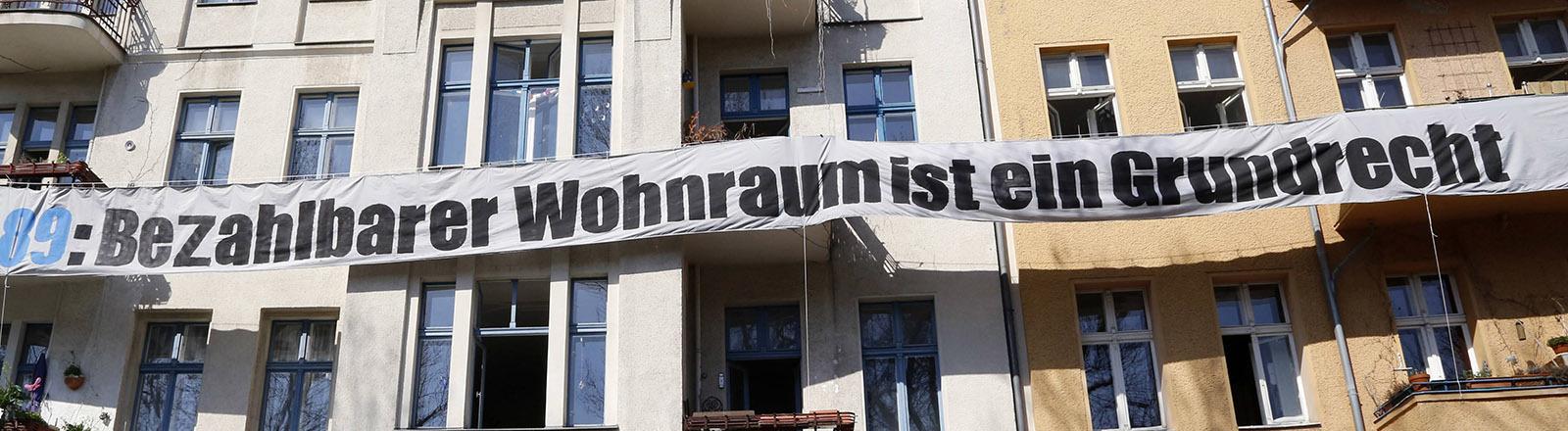 """Ein Banner an einem Mietshaus in Berlin mit der Aufschrift """"Bezahlbarer Wohnraum ist ein Grundrecht"""""""