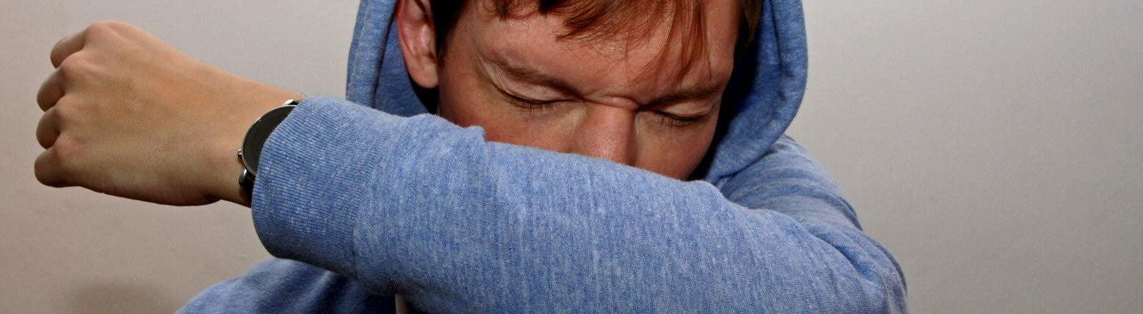 Ein Mann niest in seinen Arm