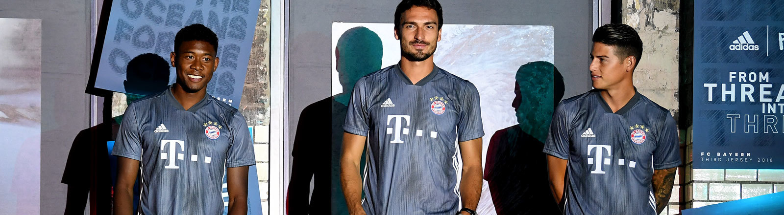 Drei Spieler des FC Bayern München präsentieren das neue Trikot