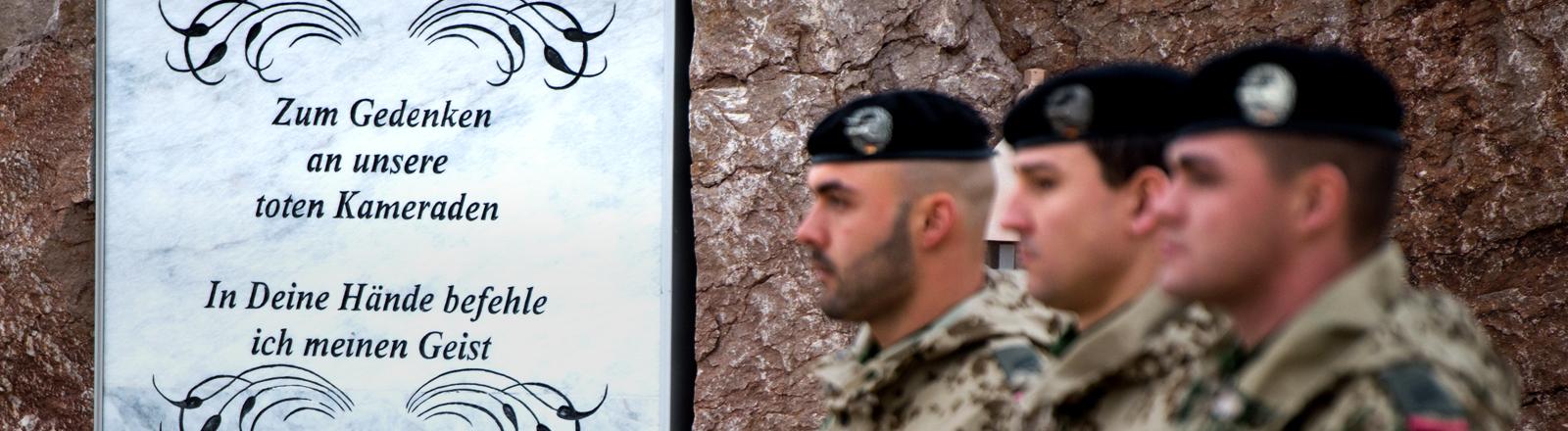 Drei Soldaten salutieren vor einer Gedenktafel in Afghanistan