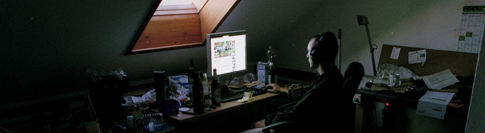 Tino sitzt in seinem dunklen Zimmer vor dem Rechner, von oben fällt Licht durchs Fenster.