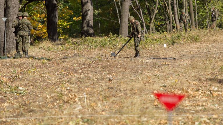 Ein polnischer Soldat sucht mit einem Metalldetektor nach alten Bomben in der Nähe der Stelle, wo der Goldzug vermutet wird.