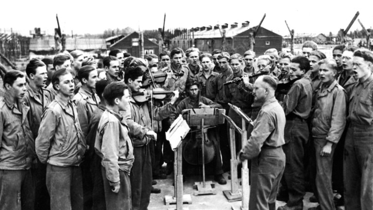 Eine Gruppe deutscher Kriegsgefangener in einem Lager der Amerikaner beim Singen.