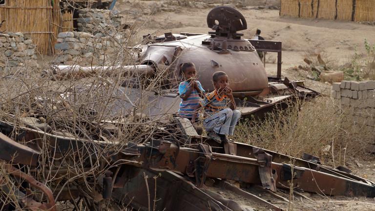 Kinder spielen auf dem Land mit liegengebliebenen Panzern.