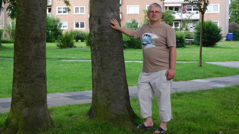Rainer Hagen steht neben einem Baum