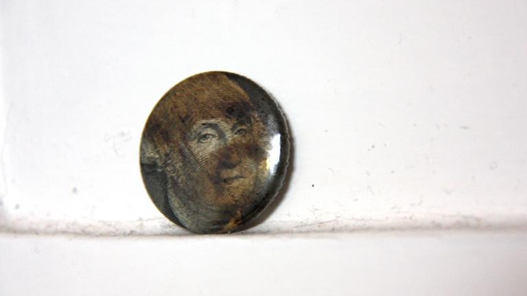 Ein Button des Künstlers Ruppe Koselleck, gemacht aus einem Ein-Dollar-Schein und Rohöl.