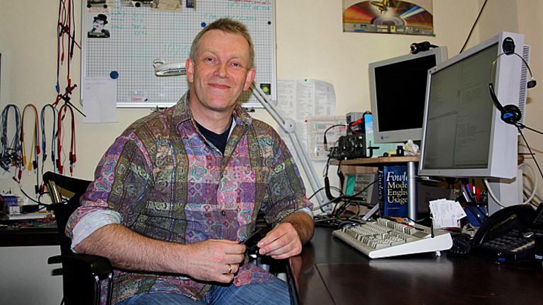 Werner Koch sitzt auf einem Bürostuhl in seinem Büro.