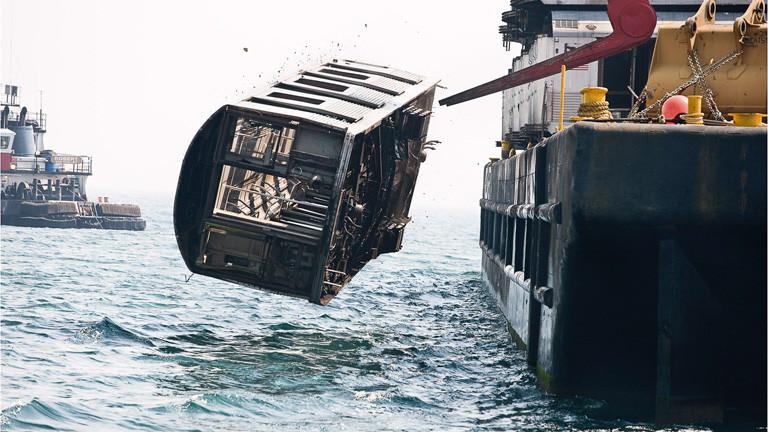 Ein Wagon wird von einem Boot ins Wasser entladen