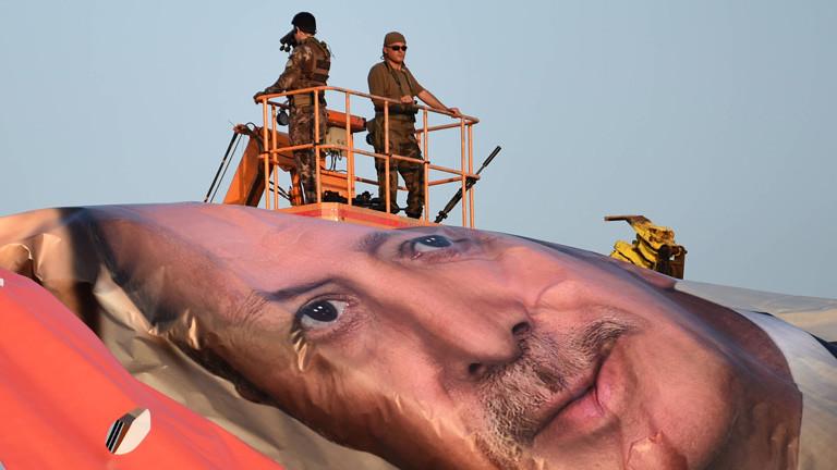 Ein aufgerolltes riesiges Banner von Präsident Erdogan, daneben Soldaten
