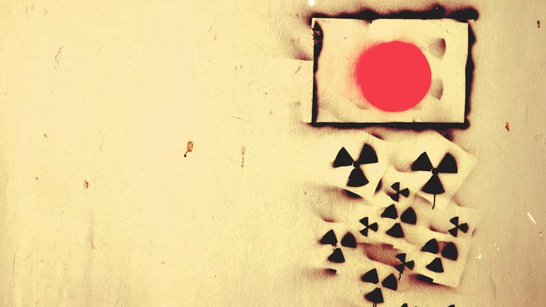 Die japanische Flagge an die Wand gesprüht, aus ihr heraus fallen kleine Atomsymbole.