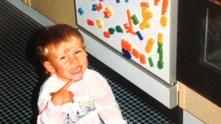 Kinderfoto von Julia Schmitz vor einer Tafel mit Magnetzahlen und -buchstaben