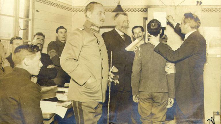 Menschen stehen herum, einer spricht in ein Megaphon, sein Kopf wird dabei festgehalten.