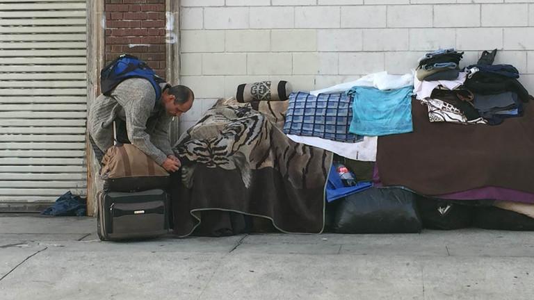 Ein Mann vor einer provisorischen Behausung auf der Straße.