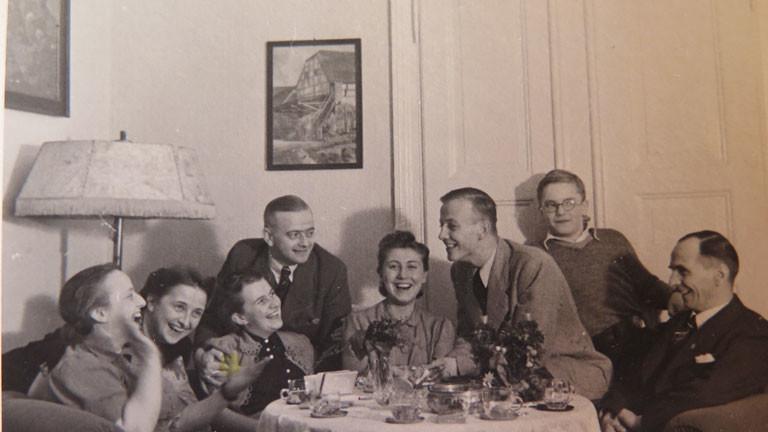 Menschen sitzen um einen runden Tisch und feiern.