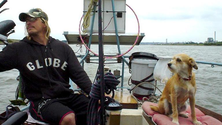 Ein Mann mit Hund auf einem Boot.
