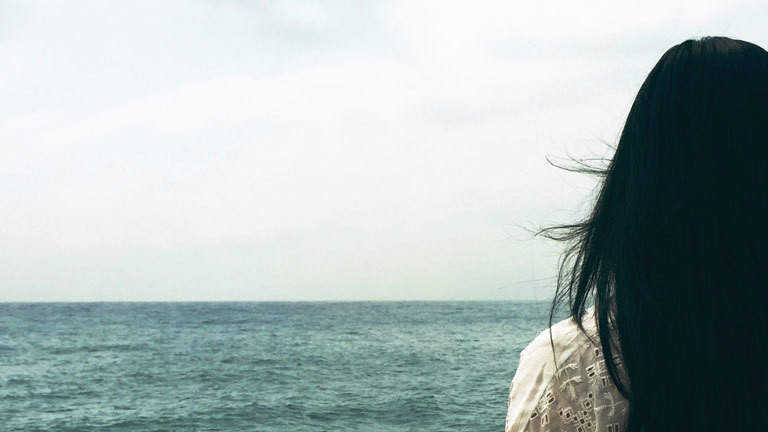 Eine Frau steht einsam vor dem meer