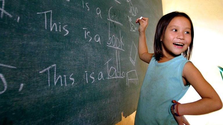 Ein Mädchen mit asiatischen Gesichtszügen schreibt englische Worte an eine Tafel.