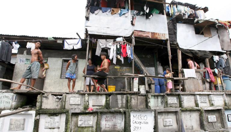 Menschen und Hütten in Manila auf dem Friedhof.