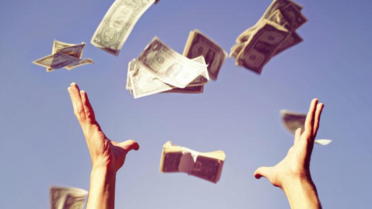 Eine Person wirft Dollarscheine in die Luft.