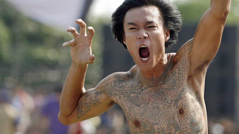 Ein tätowierter Mann auf dem Wai-Kru-Tattoo-Festival in Wat Bang Phra macht gefährliche Grimassen und Gesten.