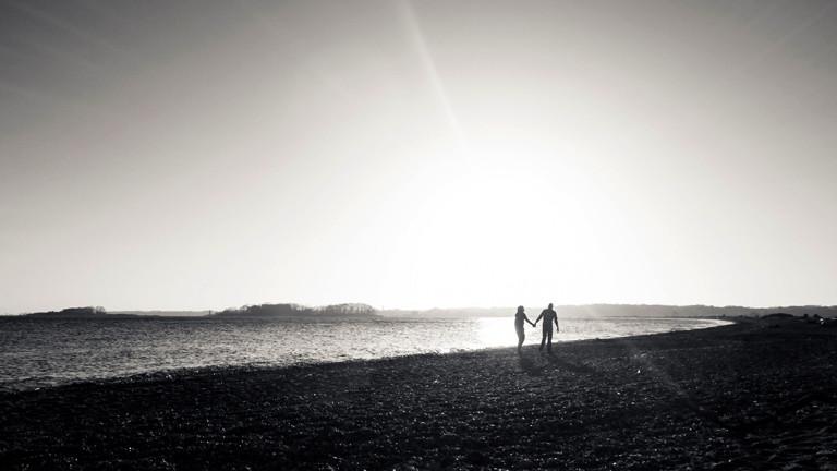 Ein Paar Hand in Hand am Strand.