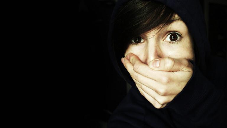 Eine Frau hält sich die Hand vor den Mund.