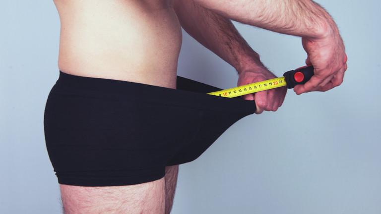 Mann hält Maßband in seine Unterhose