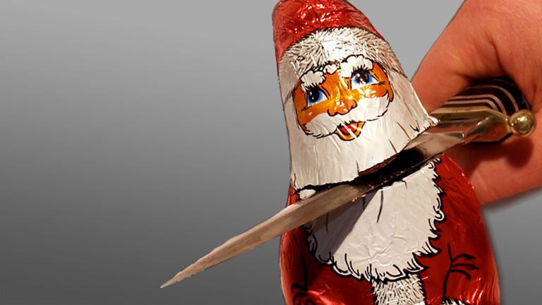 Eine Person schneidet mit einem Messer einem Schokoladen-Weihnachtsmann den Kopf ab.