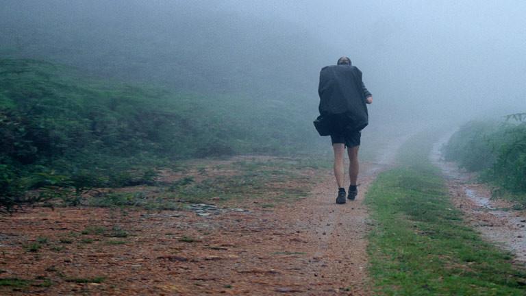 Ein Wanderer mit Rucksack im Nebel.