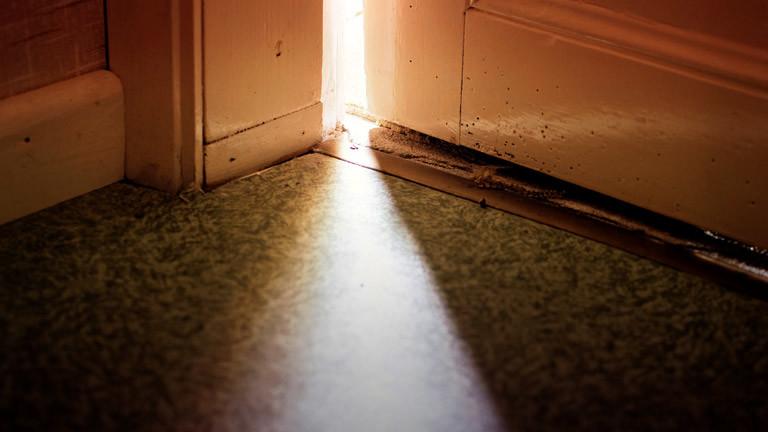 Eine Tür steht einen Spalt weit offen. Dadurch fällt Licht.