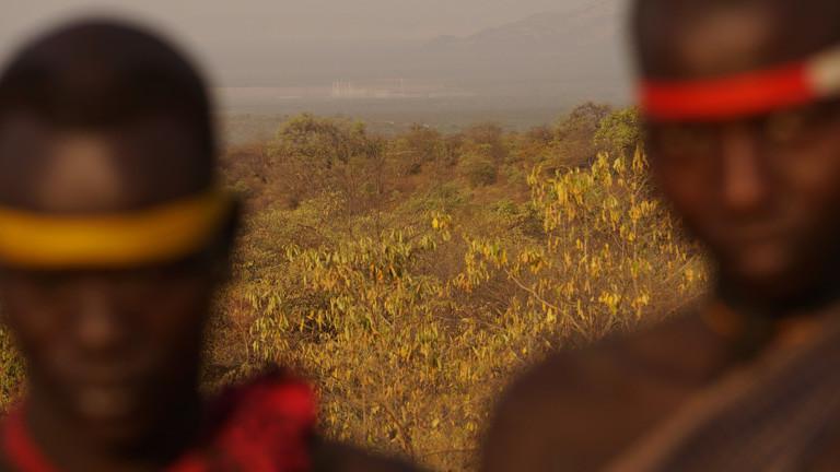 Zwei Stammesmitglieder, im Hintergrund das Staudammprojekt