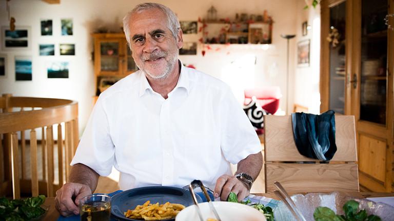 Mann sitzt vor einem Teller mit Pommes und Salat.