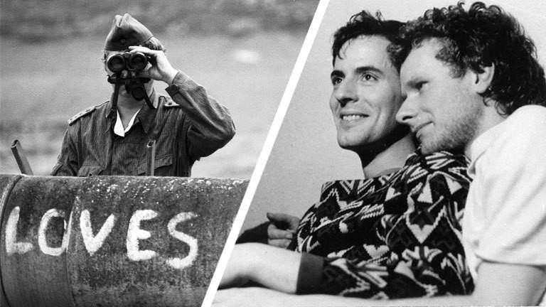 """Links zu sehen Andreas und Franz, die einander umarmen. Links ein Bild von der Berliner Mauer, auf der steht """"Loves You"""" dahinter zwei Grenzsoldaten, die durch ein Fernglas gucken."""