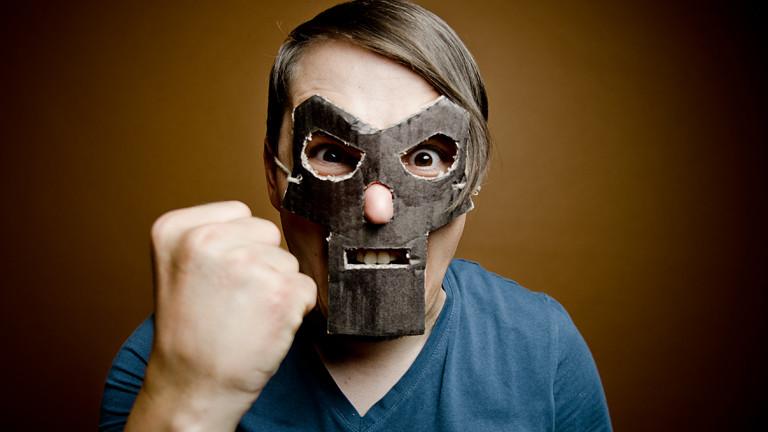 Mann mit Maske zeigt eine Faust.