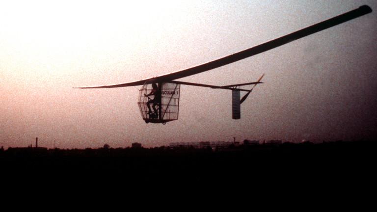 Ein Mann sitzt in einem Käfig auf einer Art Fahrrad, an das 20 Meter breite Flügel und ein Heck mit Propeller montiert sind