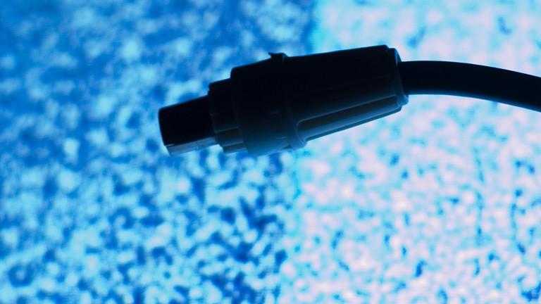 Ein gezogener Stecker vor einem Störungsbildschirm
