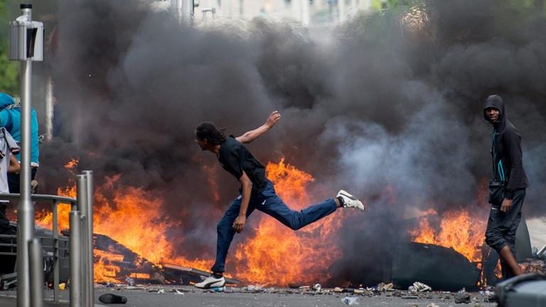 Auf der Straße brennen Gegenstände, dazwischen laufen junge Männer und werfen weitere Brandsätze.