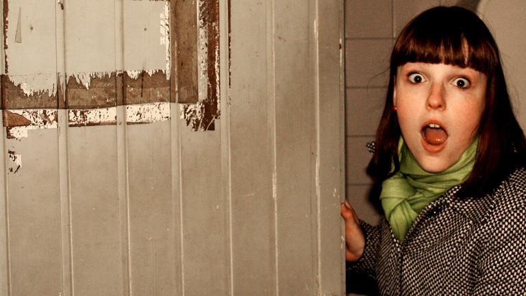 Eine junge Frau öffnet die Tür und guckt erstaunt.