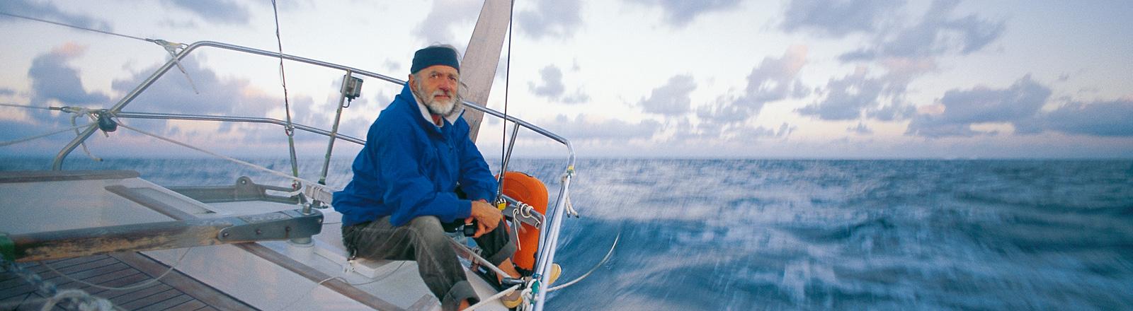 Mann sitzt auf einem Seegelboot