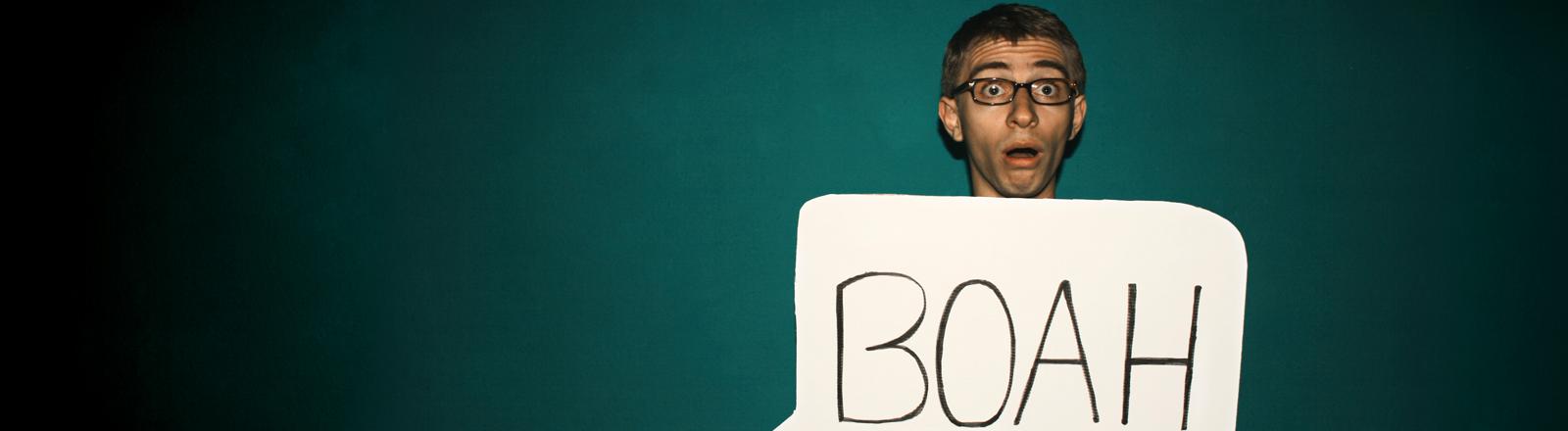 """Ein Mann guckt ungläubig und hält ein Schild mit """"Boah"""" in der Hand"""