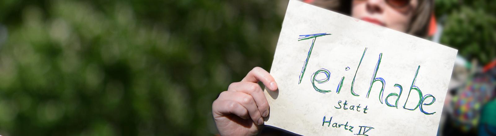 """28.04.2018, Baden-Württemberg, Karlsruhe: Eine Frau hält einen Zettel mit der Aufschrift """"Teilhabe statt Hartz IV"""" bei einer Demosntration vor dem Treffen von Bundesgesundheitsminister Spahn mit der Hartz-IV-Kritikerin Schlensog. Schlensog initiierte eine Online-Petition, mit der Gesundheitsminister Spahn aufgefordert wird, Hartz IV selbst auszuprobieren. Foto: Sina Schuldt/dpa"""